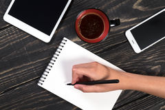 Hand writes a black pen in a white notepad Royalty Free Stock Photos