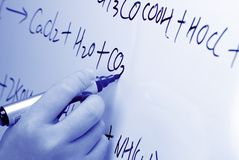 Hand writes a chemical formula on a whiteboard. Royalty Free Stock Photo