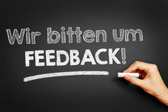 Hand writes in German `Wir bitten um Feedback!` Stock Photos