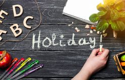 The hand writes holidays on a black board of wooden boards. The concept of an elementary school. Creative chaos. Student`s desk t stock image