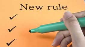 Hand writes marker on orange paper, text, message, new rules, art, study, creativity, design stock photo