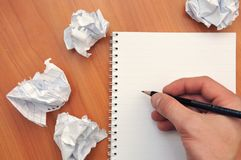 Hand writes in a notebook around a crumpled paper Royalty Free Stock Photography