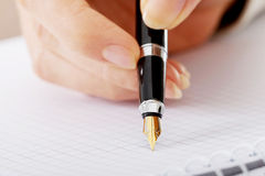 Hand writes with a pen in a notebook Stock Photography