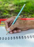 Hand writes a pen in a notebook. Handwriting, hand writes a pen in a notebook Royalty Free Stock Images