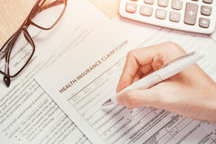 Hand writes the personal information on the health insurance claim form.  Stock Images