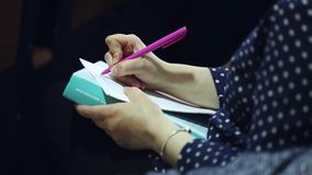 Hand writes. A woman writes in a notebook at a lecture stock video