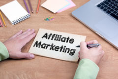 Hand writing Affiliate Marketing. Office desk with a laptop and Stock Image