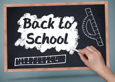 Hand writing back to school on blackboard with chalk and rulers Royalty Free Stock Images
