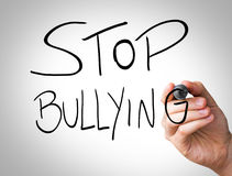 Hand writing with black and blue marker on transparent wipe board - Stop Bullying Stock Photos