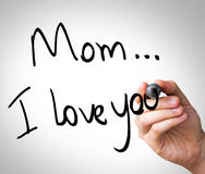 Hand writing with black mark on a transparent board - Mom, I love You.  royalty free stock photography