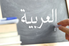 Hand writing on a blackboard in an Arabic class. Some books and school materials Stock Photos