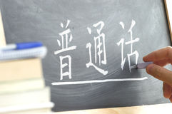 Hand writing on a blackboard in a Chinese class. Stock Photo