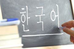 "Hand writing on a blackboard in a Korean class with the word ""Korean"" wrote in. Stock Images"
