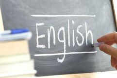 Hand writing on a blackboard in a language class with the word 'English' written on it. royalty free stock images