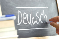 Hand writing on a blackboard in a language class with the word 'German' written on it. Royalty Free Stock Images