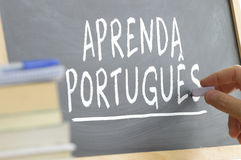 Hand writing on a blackboard in a Portuguese class. Royalty Free Stock Images
