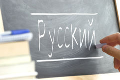 Hand writing on a blackboard in a Russian class. Royalty Free Stock Photos