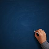 Hand writing on blank blue chalkboard Royalty Free Stock Image