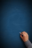 Hand writing on blank blue chalkboard. Or background stock photo