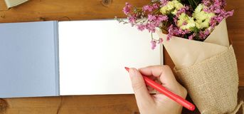 Hand writing on blank note book paper and flower bouquet on wood. Background, mock up, template Stock Photo