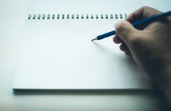 Hand writing on blank notebook. With pencil, with copy space Royalty Free Stock Photo