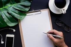 Hand Writing on blank notepaper with accessories laying on black Stock Photography