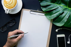 Hand Writing on blank notepaper with accessories laying on black Stock Photos