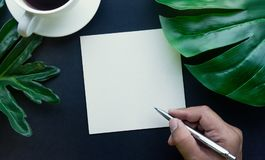 Hand Writing on blank notepaper with accessories laying on black Royalty Free Stock Photography