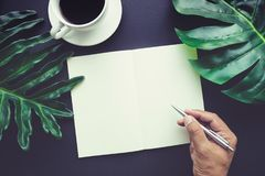 Hand Writing on blank notepaper with tropical leaves Stock Photography