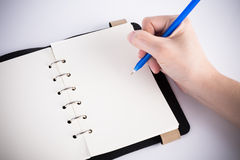 A hand is writing on blank page. Notebook Royalty Free Stock Photos