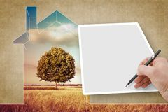 Hand writing on a blank sheet against a rural scene with a tree and a house outline - concept image with copy space royalty free stock photos