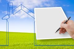 Hand writing on a blank sheet with a house outline against a green area - concept image with copy space.  royalty free stock photos