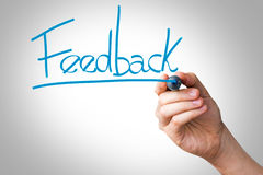 Hand writing with a blue mark on a transparent board - Feedback Royalty Free Stock Image