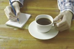 Hand writing on book while drinking black coffee. Cup Royalty Free Stock Photos