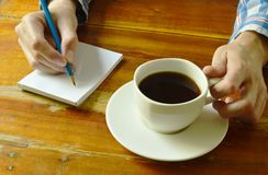 Hand writing on book while drinking black coffee. Cup Stock Photography