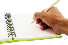Hand writing on book. Pencil in hand writing on the notebook Stock Images