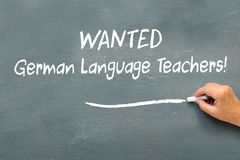 Hand writing on a chalkboard Wanted German language teachers. Hand writing on a chalkboard the  words Wanted German language teachers. Refugee crisis in Europe Royalty Free Stock Image