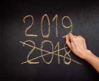 Hand writing 2019 and crossing out 2018 stock image