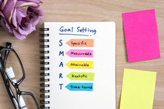 Hand writing definition for smart goal setting on notebook. With eye glasses, purple rose and colorful sticky note on desk stock images