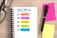 Hand writing definition for smart goal setting on notebook. With pen, eye glasses and colorful sticky note on desk stock photography