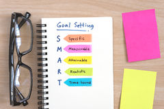 Hand writing definition for SMART goal setting. On open notebook with eye glasses and colorful sticky note on office desk table stock images