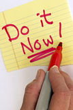 Hand Writing Do it Now. Here is a note saying to not wait and get in done now.  Don't procrastinate!  It's important to get your jobs done and not put it off Stock Photography