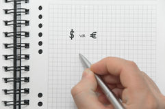 Hand writing dollar and euro symbols. Hand writing underneath dollar and euro symbols on white spiral notebook with elegant silver pen Royalty Free Stock Photography