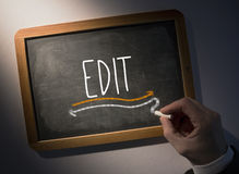 Hand writing Edit on chalkboard. Hand writing the word edit on black chalkboard stock images