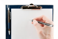 Hand writing on an empty document in a clipboard Royalty Free Stock Image