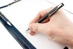 Hand writing on an empty document in a clipboard Stock Photos