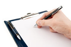 Hand writing on an empty document in a clipboard Royalty Free Stock Images