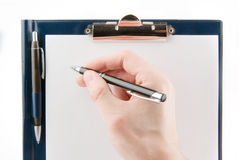 Hand writing on an empty document in a clipboard Royalty Free Stock Photos