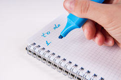 Hand writing on empty notepad, white background Stock Photos