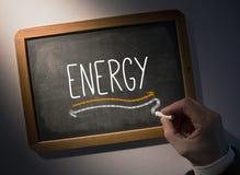 Hand writing Energy on chalkboard. Hand writing the word energy on black chalkboard Stock Images